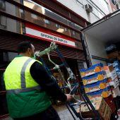 Un operario descarga la mercancía de un camión junto una oficina de empleo en Madrid
