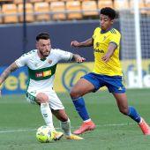 El centrocampista del Elche CF Josan lucha por el balón con el delantero del Cádiz CF Lozano