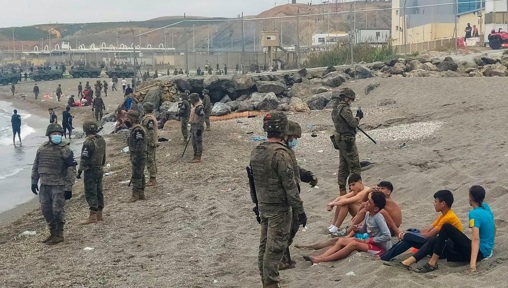 Miembros del Ejército observan a un grupo de inmigrantes que ha llegado a nado en los espigones fronterizos de Ceuta.