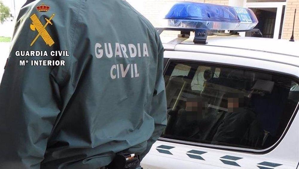 Un agente de la Guardia Civil junto a un coche patrulla.