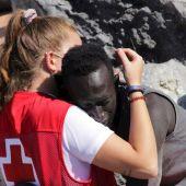 Una trabajadora de Cruz Roja abraza a un inmigrante que ha cruzado los espigones fronterizos