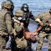 Militares trasladando a uno de los inmigrantes que ha entrado en Ceuta a nado