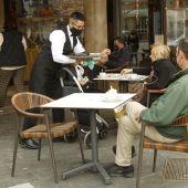 Un camarero atiende a varios clientes en la terraza de un bar en Palma.