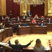 El diputado del PP Sebastià Sagreras tomando la palabra mientras el vicepresidente Yllanes levanta los brazos en gesto de protesta, durante el pleno de este martes en el Parlament.