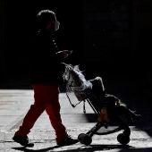 Un hombre pasea con un carrito de bebé por la ciudad de Valencia.