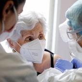 dos sanitarias poniendo una vacuna a una residente de un centro de mayores