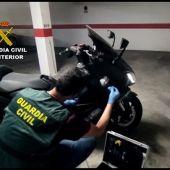 Un agente de la Guardia Civil junto a una de las motocicletas que adquirió el detenido.