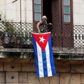 Una mujer sale al balcón donde se expone una bandera cubana