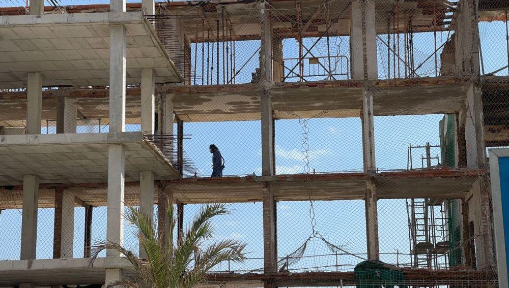 Un trabajador en el interior de las ruinas del viejo hotel de Arenales del Sol de Elche.
