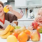 Dos niños comiendo fruta