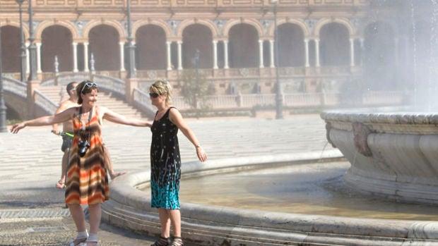 Turistas refrescándose en la Plaza de España
