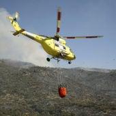 Un helicóptero lleva agua para arrojar sobre el incendio