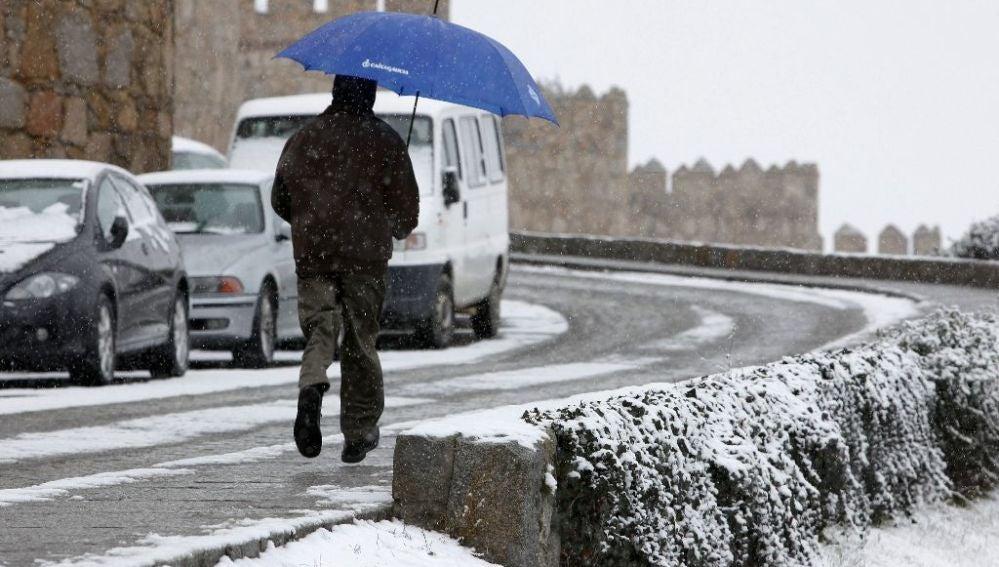 Un hombre corre con un paraguas para protegerse de la nieve en Ávila