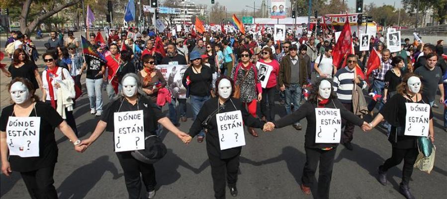 Miles de personas con fotografías de desaparecidos marchan en el 40 aniversario del golpe de Pinochet