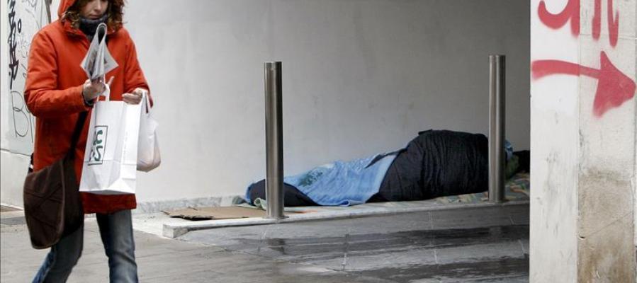 Un indigente duerme resguardado en un portal del centro de Valencia