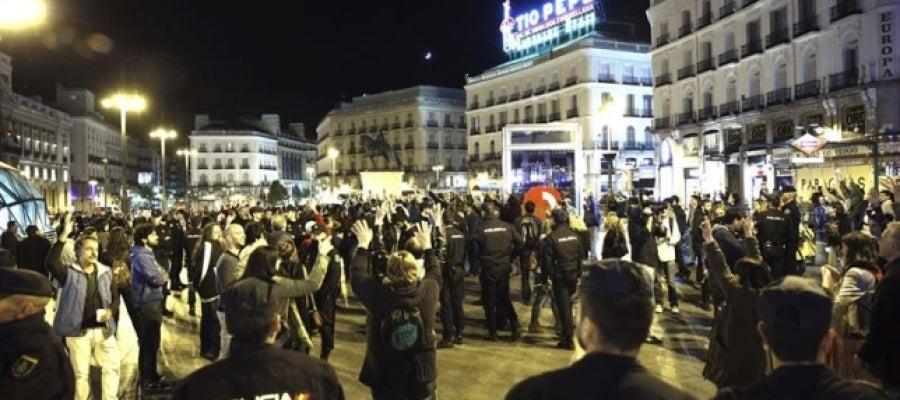 Miembros del movimiento 15M, vigilados por policías nacionales en la Puerta del Sol