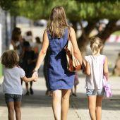 Una madre paseando con sus dos hijos