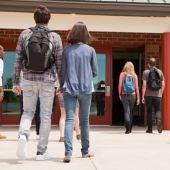 Una pareja de adolescentes entrando al instituto