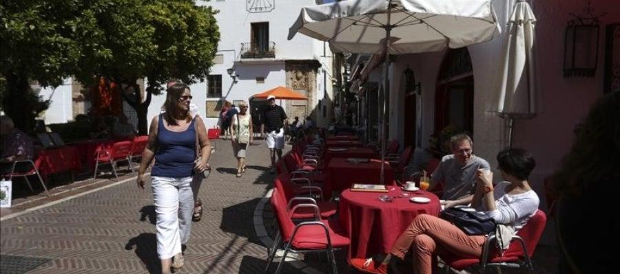 Algunos turistas se refrescan sentados en una terraza de Marbella
