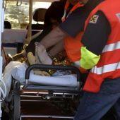 Los servicios médicos, ayudados por un bombero, atendiendo en un accidente
