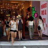 Varias personas entrando y saliendo de una tienda en época de rebajas