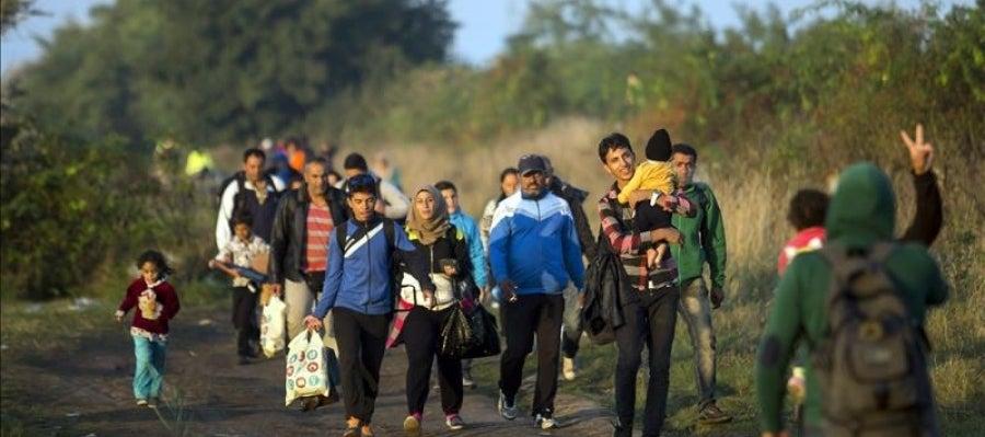 Varios refugiados caminan por las vías del tren en Hungría