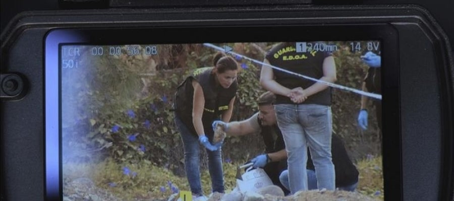 Monitor de una cámara de televisión en la que se aprecia a varios agentes recogiendo los restos óseos