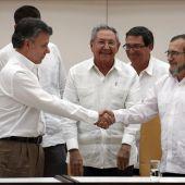 Juan Manuel Santos y Timochenko en presencia de Castro