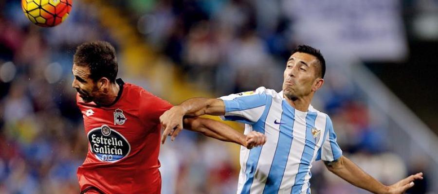 El defensa del Deportivo, Fernando Navarro, disputa un balón con el delantero brasileño del Málaga, Charles Dias