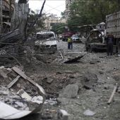 Varias personas inspeccionan el lugar donde se ha producido un ataque aéreo en Siria