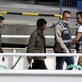 Un refugiado es escoltado por la policía griega para su exportación