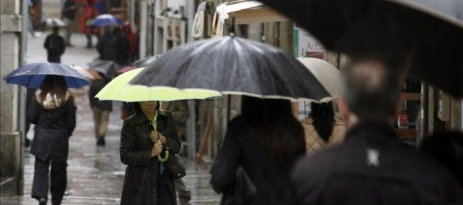 Varias personas se protegen de la lluvia con paraguas