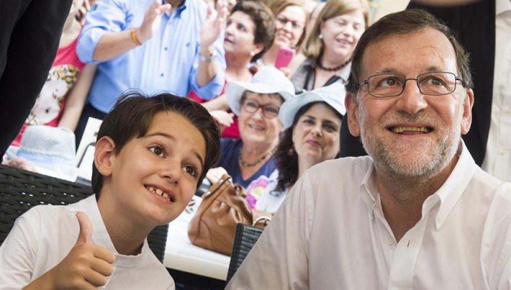 Mariano Rajoy acompañado de un niño durante un mitin en Murcia