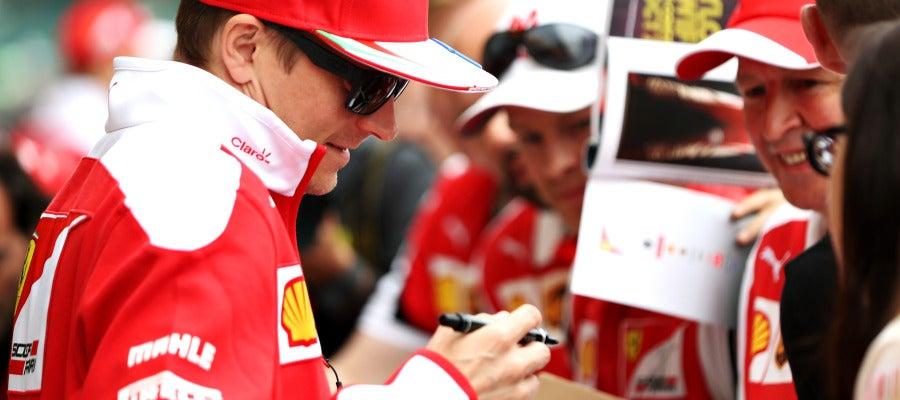 Kimi Raikkonen firma un autógrafo a un aficionado
