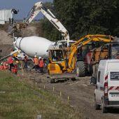 Un grupo de operarios trabajan en la construcción de un muro en la ciudad septentrional francesa de Calais, Francia