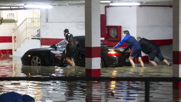 Varias personas intentan sacar el coche de un garaje inundado