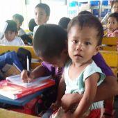 Un niño filipino de nueve años con su hermano de dos en la escuela