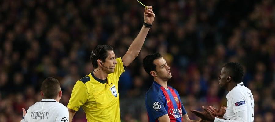 Aytekin muestra una tarjeta amarilla durante el Barcelona - PSG