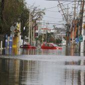 Dos coches flotan en una calle totalmente inundada en San Juan (Puerto Rico), tras el paso del huracán María.