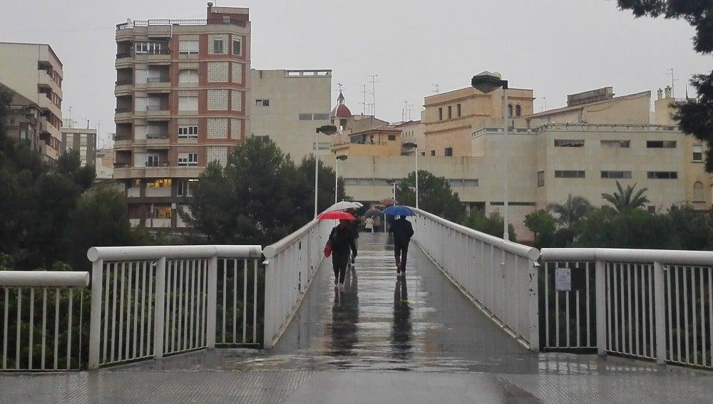 Personas con paraguas en la Pasarela del Mercado de Elche.