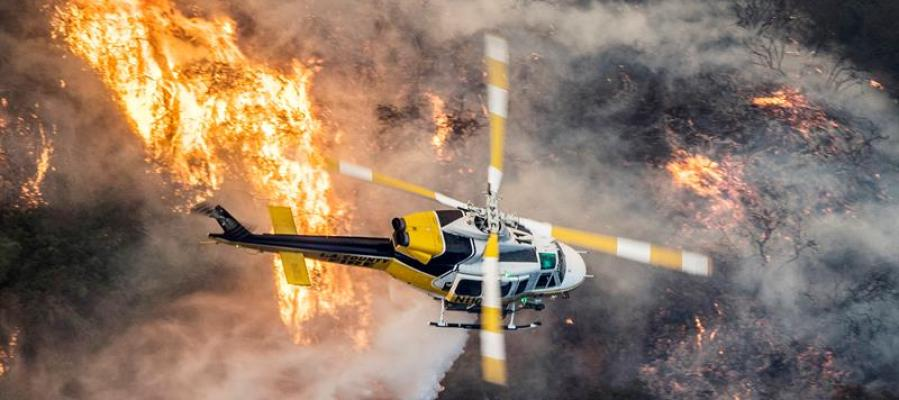 Un helicóptero de bomberos del Condado de Los Ángeles sobrevuela un gran incendio