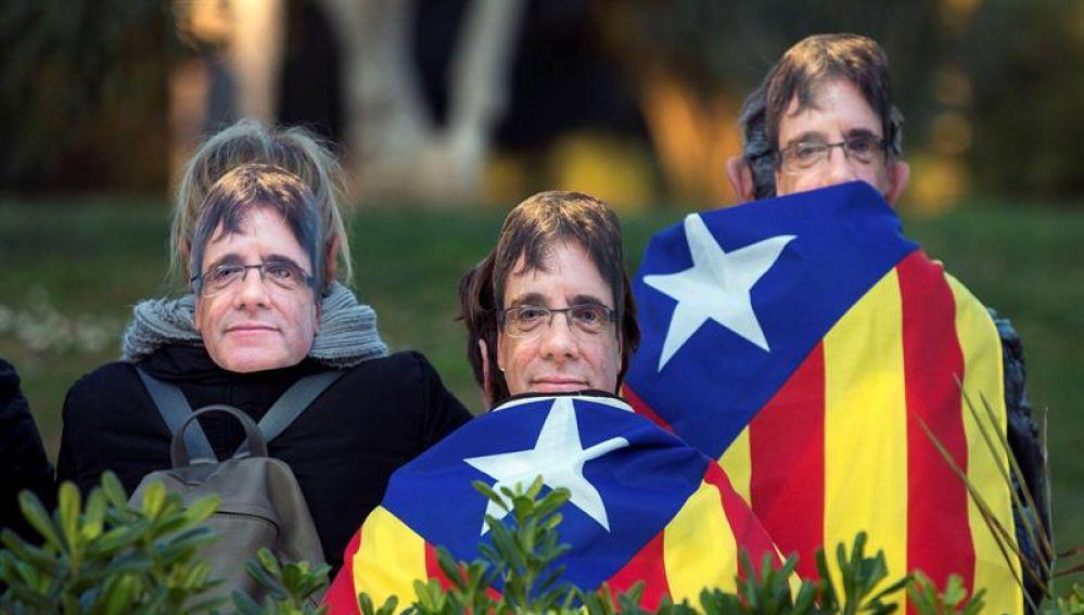 Gente con caretas de Puigdemont en los alrededores del Parlament
