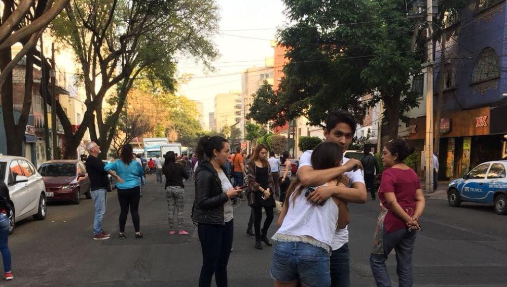 Personas esperan afuera de sus oficinas y vehículos tras el sismo registrado