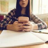 Una adolescente mira su móvil en clase