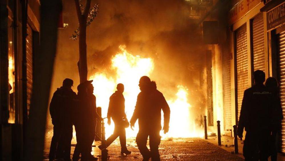 Contenedores incendiados en la calle Mesón de Paredes con la calle del Oso, en el barrio de Lavapiés