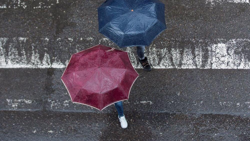 Dos personas cruzando un paso de cebra con paraguas