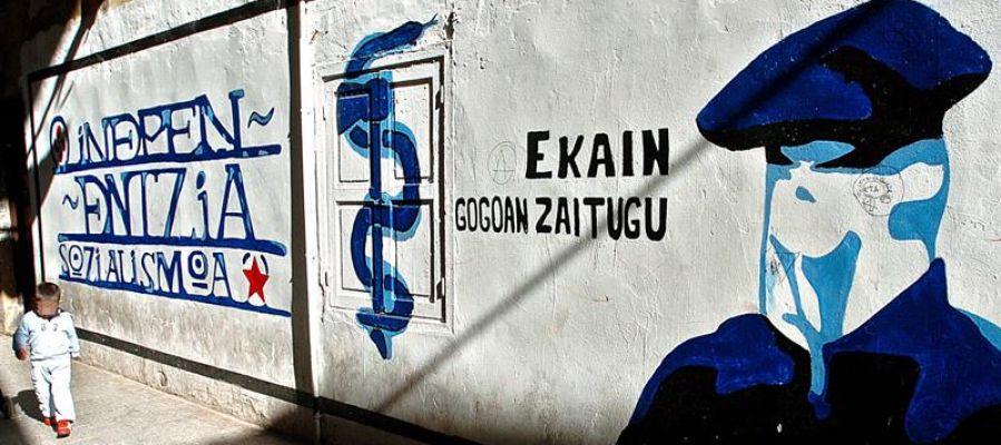 Mural que representa a un encapuchado junto al anagrama de ETA.