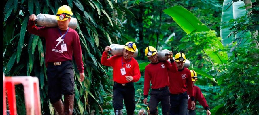 Miembros de los servicios de rescate de Tailandia cargan con botellas de oxígeno