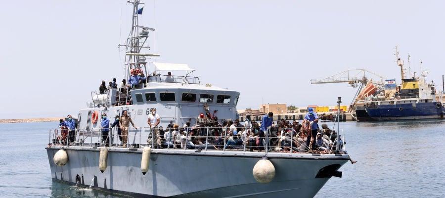 Un barco de la Armada de Libia con inmigrantes a bordo llega a una base