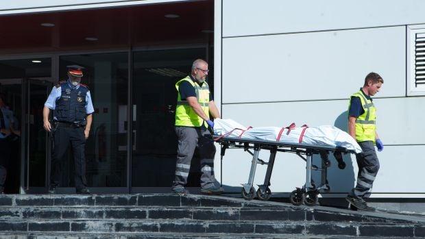 Miembros del servicio judicial retiran el cadáver del hombre que ha sido abatido